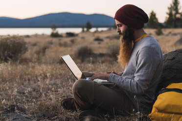 USA, North California, bearded young man using laptop near Lassen Volcanic National Park - KKAF02992