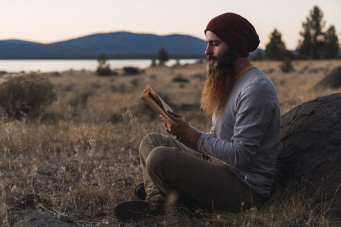 USA, North California, bearded young man reading a book near Lassen Volcanic National Park - KKAF02995