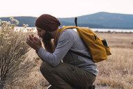 USA, North California, bearded man examining a plant near Lassen Volcanic National Park - KKAF02998