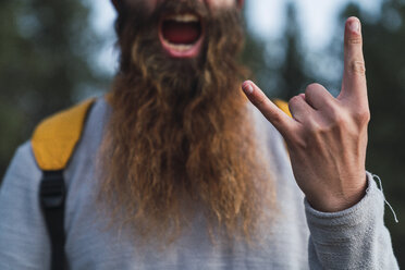 Close-up of screaming man with beard making horn sign - KKAF03004