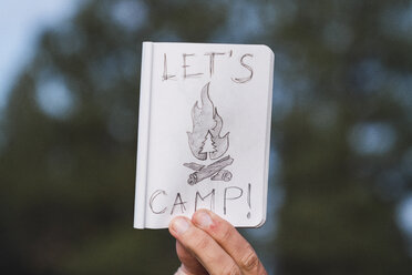 Hand in a forest holding 'Let's Camp' sign - KKAF03007