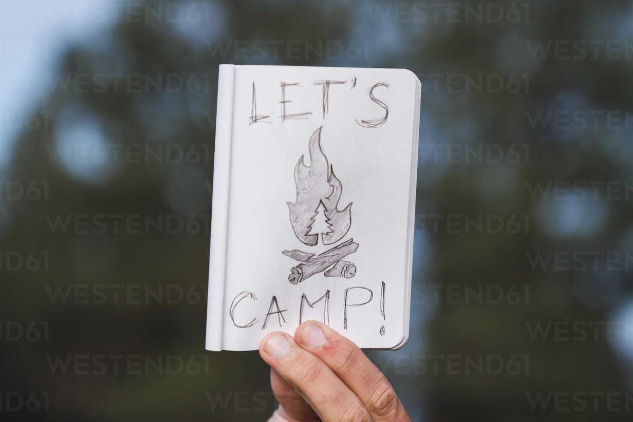 Hand in a forest holding 'Let's Camp' sign - KKAF03007 - Kike Arnaiz/Westend61
