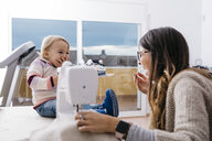 Happy mother with little daughter at home using sewing machine - JRFF02083