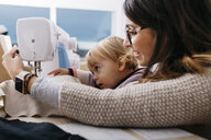 Happy mother with little daughter at home using sewing machine - JRFF02086