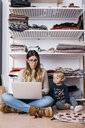 Llittle daughter watching mother sitting on the floor at home using laptop - JRFF02095