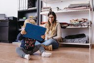 Mother and little daughter sitting on the floor at home using laptop and tablet - JRFF02101
