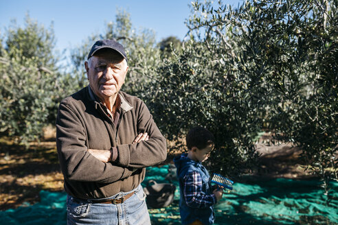 Portrait of senior man with his grandson in olive orchard - JRFF02122