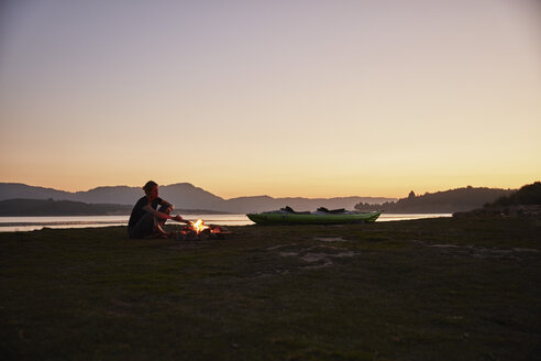 Chile, Talca, Maule River, woman sitting at camp fire beside canoe - SSCF00073
