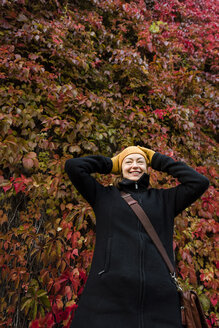 Portrait of smiling woman standing in front of wall overgrown with Virginia creeper in autumn - PSIF00166