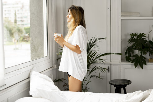 Young woman in nightwear standing at the window holding cup of coffee - ERRF00089