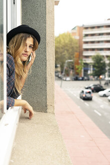 Young woman leaning out of window talking on cell phone - ERRF00095