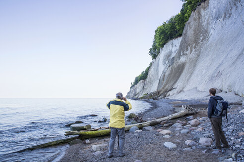 Germany, Mecklenburg-Western Pomerania, Ruegen, Jasmund National Park, hikers looking on chalk cliff at 'Kieler Ufer' - MAMF00243