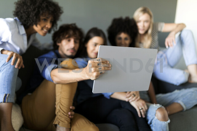Friends sitting on couch looking at tablet - VABF01736