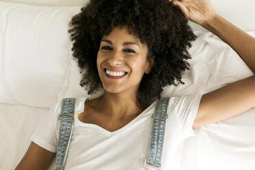 Portrait of happy woman lying in bed - VABF01751