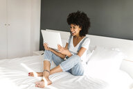 Happy woman sitting on bed looking at tablet - VABF01757