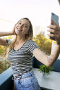 Smiling young woman taking a selfie on balcony - VABF01763