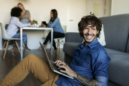 Laughing man sitting on floor using laptop with friends in background - VABF01766