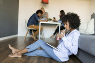 Woman with soft drink sitting on floor using laptop with friends in background - VABF01769