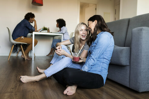 Two cheerful young women sitting on floor with cell phone and drink and friends in background - VABF01778