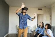 Two women watching man with VR glasses at home - VABF01793