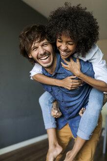 Cheerful man carrying girlfriend piggyback at home - VABF01796
