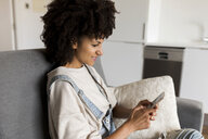 Smiling woman sitting on couch at home using cell phone - VABF01823
