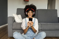 Smiling woman sitting at home with headphones and cell phone - VABF01832