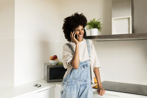 Laughing woman on cell phone in kitchen at home - VABF01838