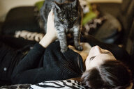 Portrait of grey tabby cat and owner on the couch at home - JATF01066