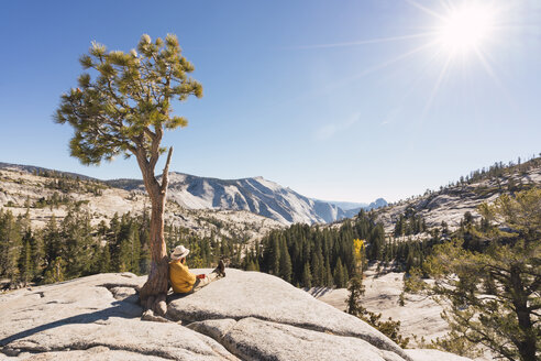 USA, California, Yosemite National Park, hiker leaning on tree - KKAF03015