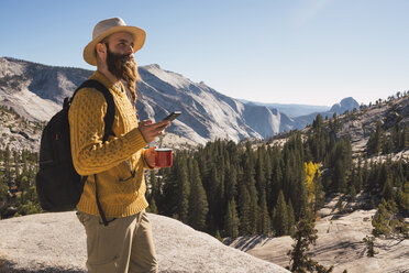 USA, California, Yosemite National Park, hiker using smartphone and holding cup - KKAF03018