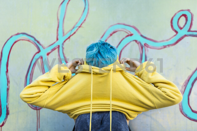 Young woman with dyed blue hair putting on yellow hooded jacket - ERRF00109 - Eloisa Ramos/Westend61