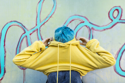 Young woman with dyed blue hair putting on yellow hooded jacket - ERRF00109