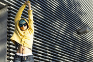 Portrait of young woman with dyed blue hair wearing sunglasses and yellow hooded jacket - ERRF00112