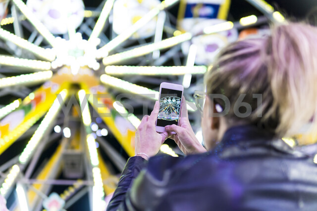 Back view of woman taking photo of big wheel with smartphone at fair - FBAF00172 - Francesco Buttitta/Westend61