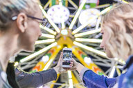 Mother and daughter taking photo of big wheel at fair - FBAF00175