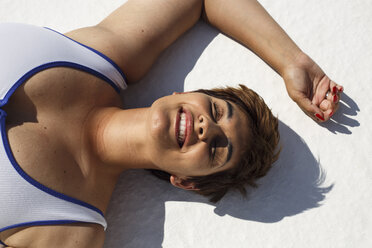 Portrait of laughing young woman taking sunbath - ERRF00117