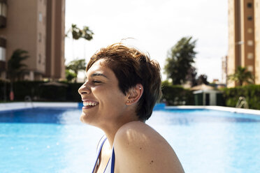 Laughing young woman with short brown hair relaxing at swimming pool - ERRF00120