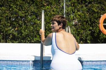 Back view of plump young woman leaving swimming pool - ERRF00123