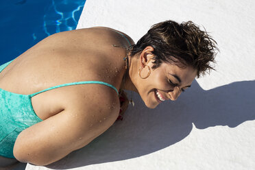Laughing young woman leaning at poolside - ERRF00135