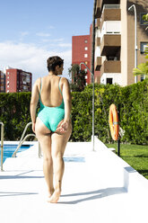 Back view of plump young woman walking next to swimming pool - ERRF00141