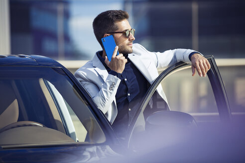 Young businessman standing at his car, talking on the phone - JSRF00075