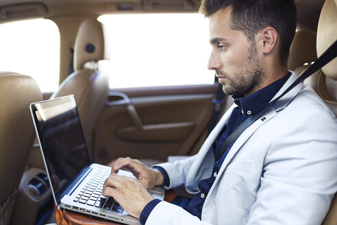 Young businessman working from the backseat of a car - JSRF00087