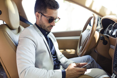 Young businessman sitting in car, using smartphone - JSRF00090