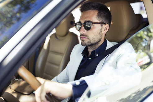Successful young businessman driving in his car - JSRF00093