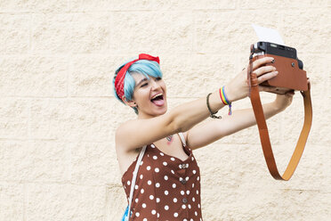Portrait of young woman with blue dyed hair taking selfie with instant camera - ERRF00143