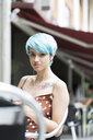 Portrait of young woman with blue dyed hair sitting in a pavement cafe listening music with earphones - ERRF00149