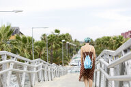 Spain, back view of young woman with blue dyed hair with backpack walking on a bridge - ERRF00152