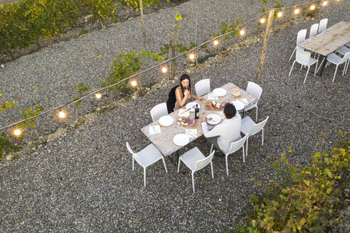 Italy, Tuscany, Siena, top view of young couple having dinner in a vineyard - FBAF00183