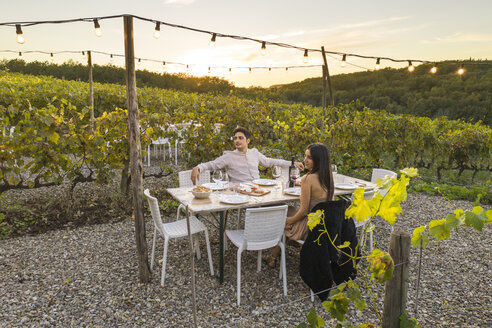 Italy, Tuscany, Siena, young couple having dinner in a vineyard - FBAF00189
